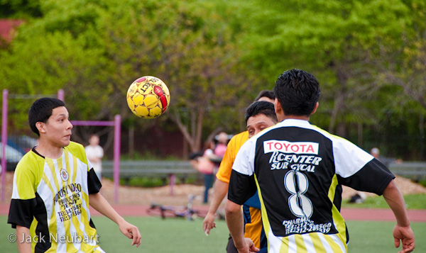 SPORTS. For this second shot, I cropped in a little to focus on the ball and players. Focal length remained constant, at 200mm (= 300mm). I should note that, even though the manual-focusing ring feels a bit gritty (typical of many AF lenses), I found I could easily focus using one or two fingers to rotate the ring while the same hand was supporting the lens. Photo Copyright  ©2009 Jack Neubart. All rights reserved.