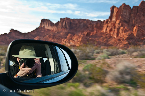 SELF-PORTRAIT. While in the passenger seat on a drive through Valley of Fire, I took this opportunity to focus the lens on my reflection in the mirror, with a wide enough focal length setting (34mm/51mm equivalent) to capture the surrounding desert scenery. Vibration Reduction was apparently at work to prevent camera shake. Photo Copyright  ©2009 Jack Neubart. All rights reserved.