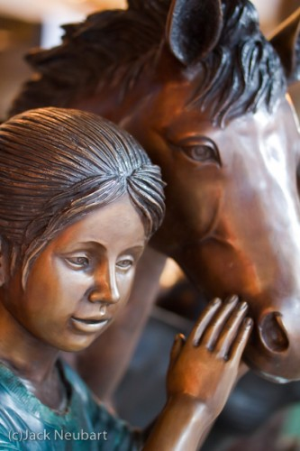 Girl & Horse. I had come upon some bronze-like, life-size plaster sculptures on the street when the light was waning. Knowing flash would throw back glaring reflections, I opted to shoot by available light. I took advantage of that wide aperture to shoot handheld, using exposures as slow as 1/50th second (ISO 800). Copyright  ©2009 Jack Neubart. All rights reserved.