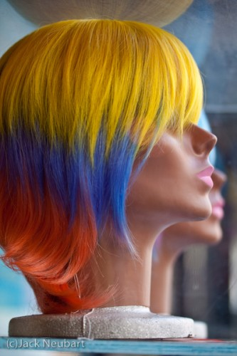 Head Shot. The wildly colored wig caught my eye when I came upon this mannequin head in a display case on the street. With enough light to expose at ISO 100, I shot wide open to blur out the surroundings and the second head, which gave me a 1/160 sec shutter speed, easily enough to prevent camera shake. Copyright  ©2009 Jack Neubart. All rights reserved.
