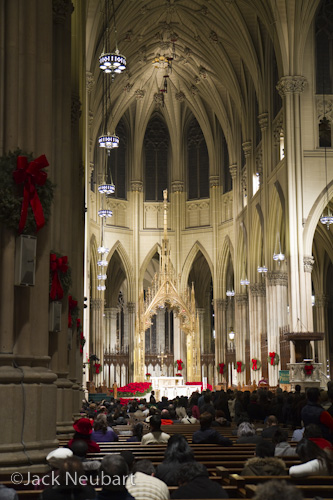 Inside St. Patrick's Cathedral. I photographed this NYC landmark shortly before Christmas, with the 7D and 17-55mm lens-handheld, with image stabilization engaged, all at ISO 400. Vertical: available light, f/2.8, 1/15 sec, at 35mm (= 56mm in 35mm equivalent). Verticals with lens tilted upward: here I shot by available light and then flash (apparent by all the brightly lit backs of heads), with the lens at 17mm (= 27mm) and an available-light exposure at 1/10 sec (1/60 with flash). Horizontals: even bounce flash (evident with the bright vaulting arch framing the sculpture) was not an ideal solution, and the existing lighting proved to be a better choice. The flash used was a Canon 580EX.  ©Jack Neubart. All rights reserved.