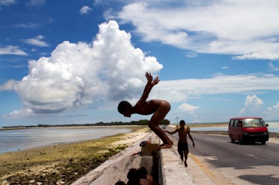Boy jumping in the water from the causeway that separates the lagoon from the ocean on the island of Tarawa. ©Malin Fezehai